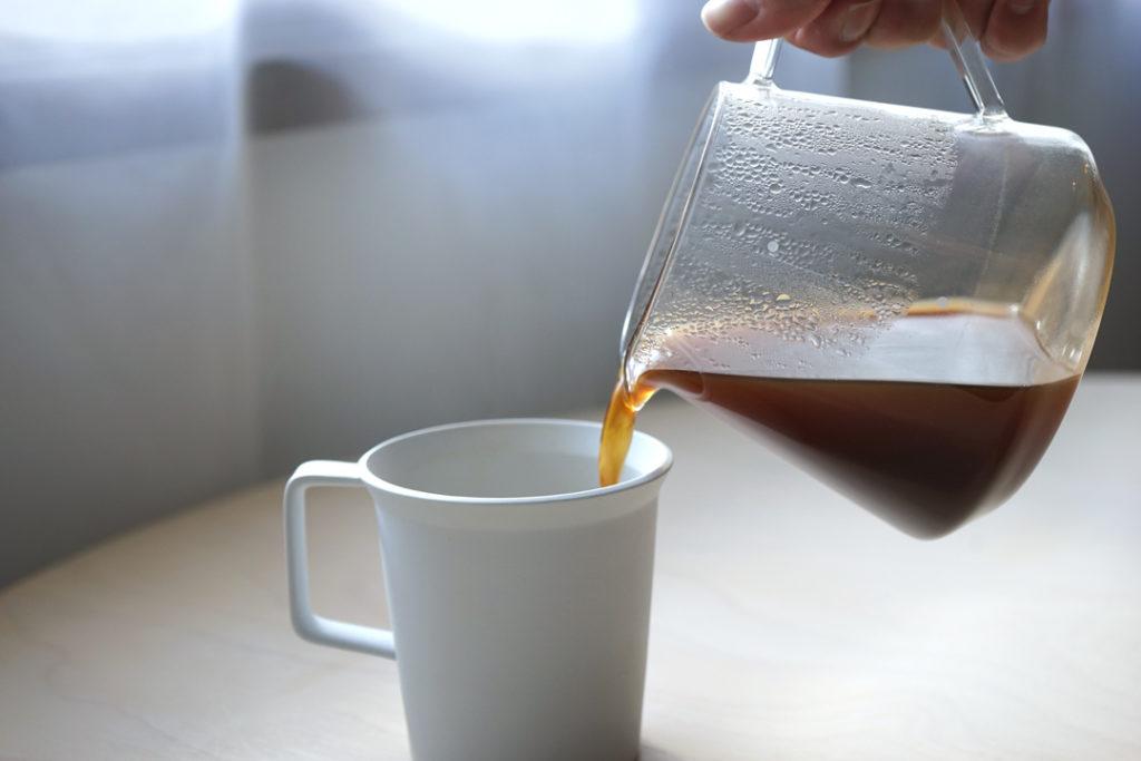 コーヒーサーバーからカップにコーヒーを注ぐ