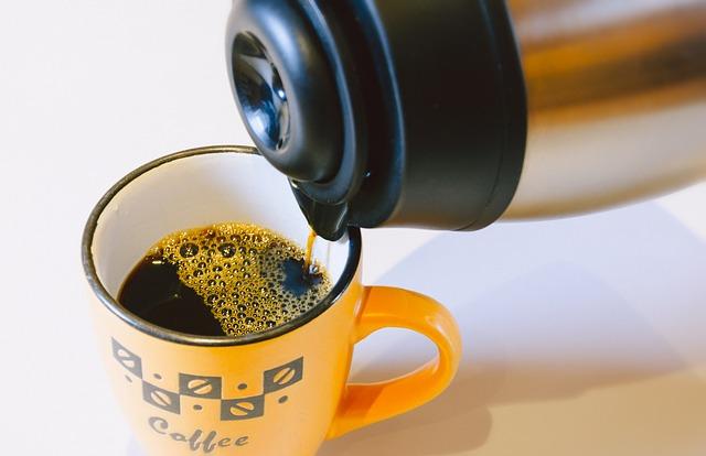 保温サーバーからマグカップにコーヒーを注ぐ