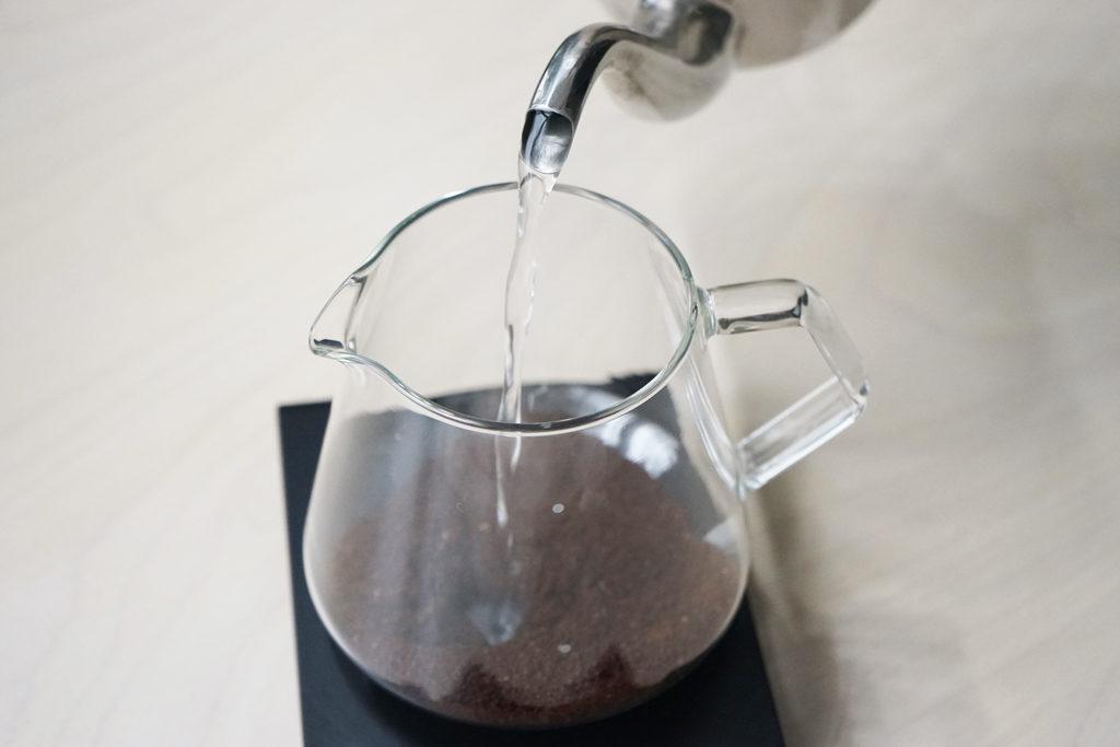 サーバーに入ったコーヒーの粉にお湯を注ぐ