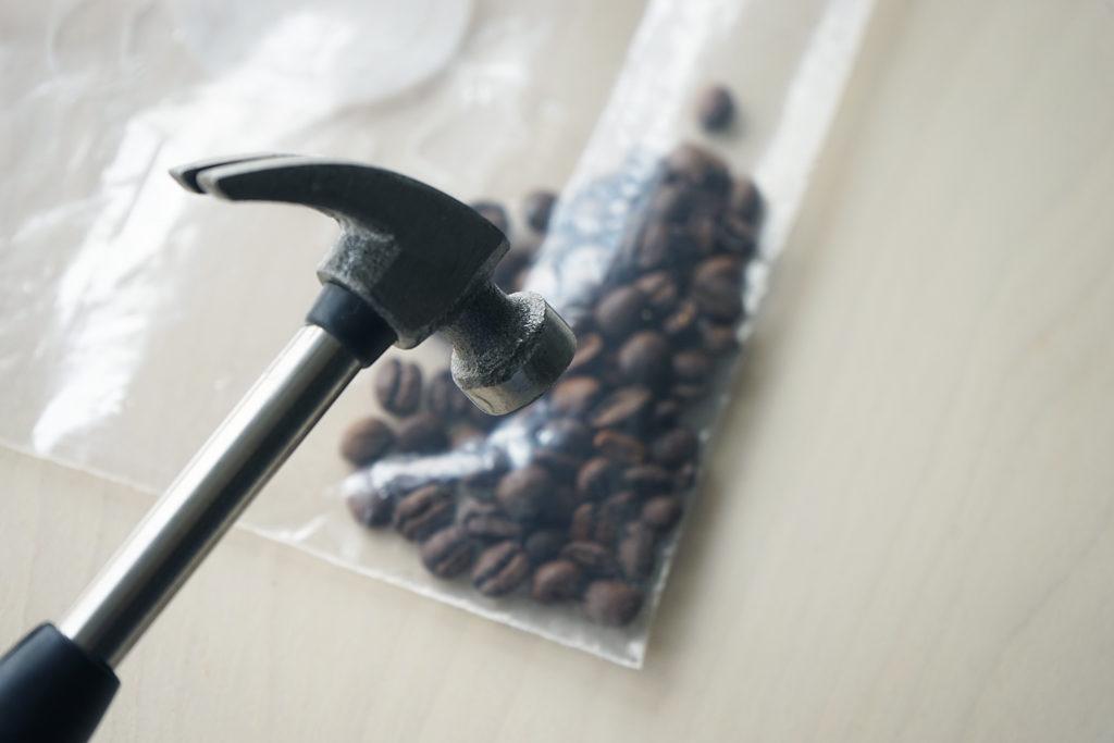 ハンマーで袋に入ったコーヒー豆を潰していく