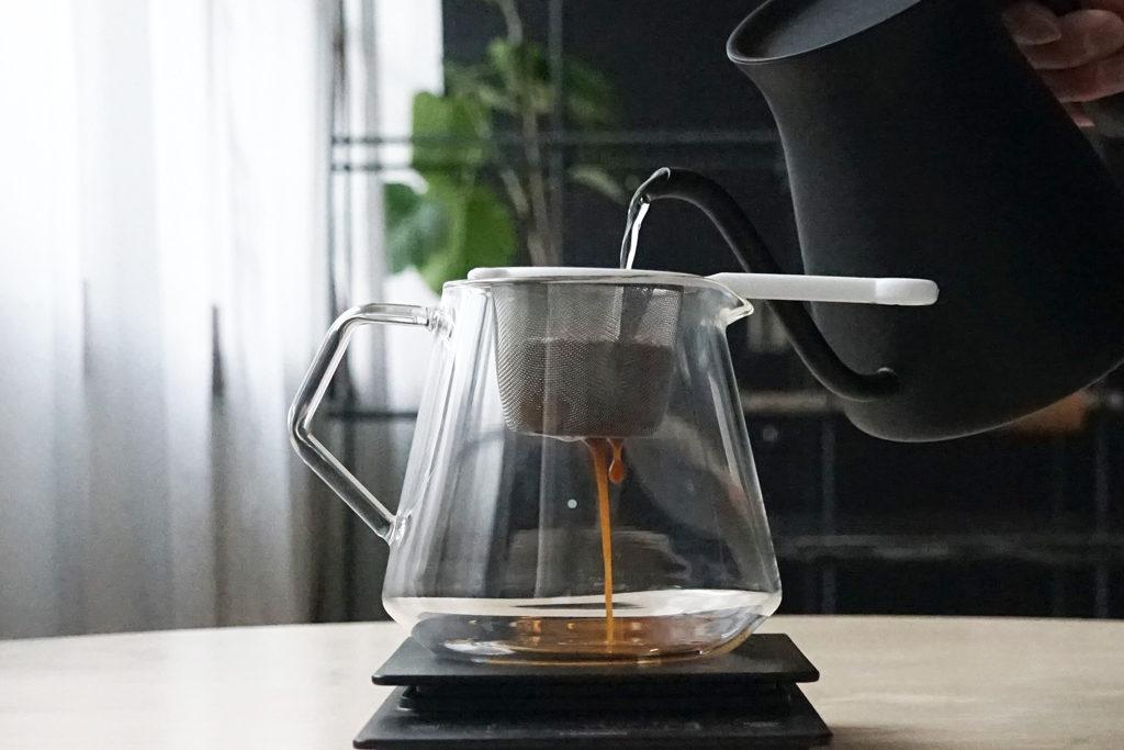 茶こしに入ったコーヒーの粉にお湯を注ぐ