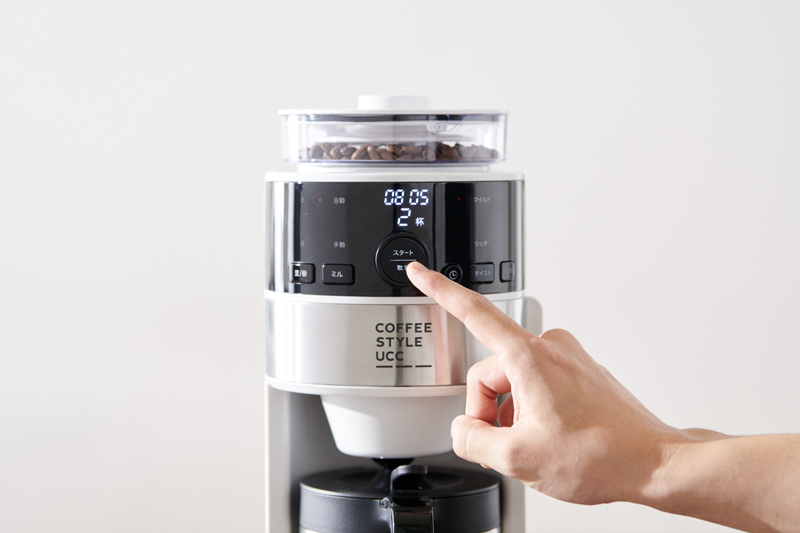 コーヒーメーカーのボタンを押す