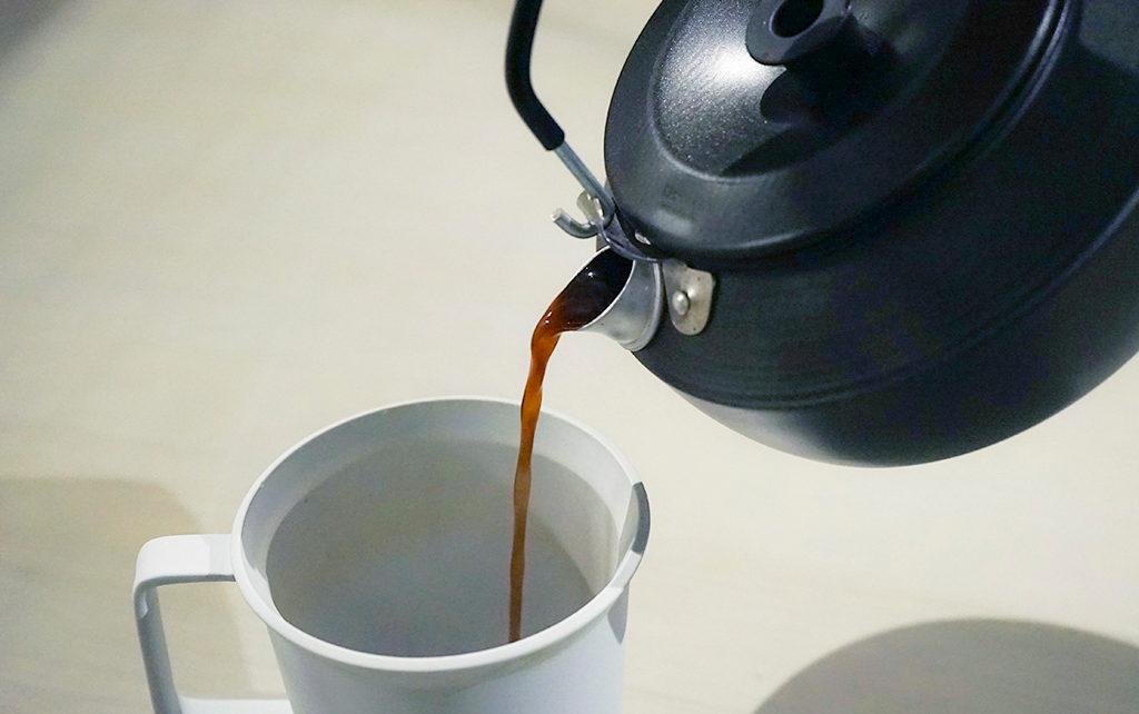 やかんからマグカップにコーヒーを注ぐ